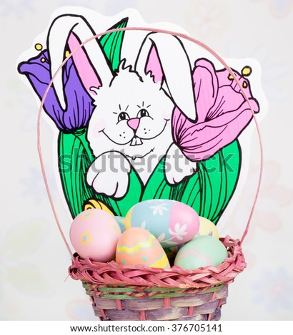 Colorful eggs in a basket with Easter rabbit decoration in background