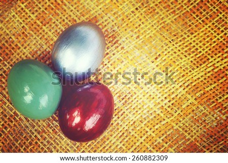 Colorful eggs on bamboo weave sheet background, Vintage style image of easter decoration with copy space on the right. - stock photo