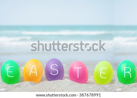 colorful eggs on white sand beach over blue sea,happy Easter or summer holiday concept. - stock photo