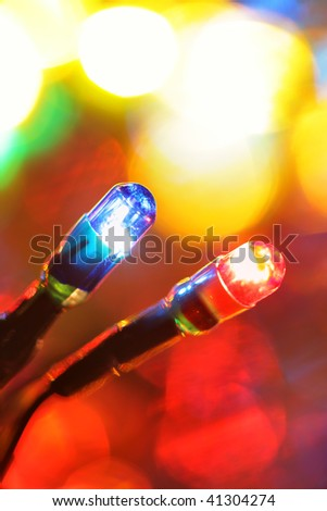 Colorful electric light bulbs and lights out of focus - stock photo