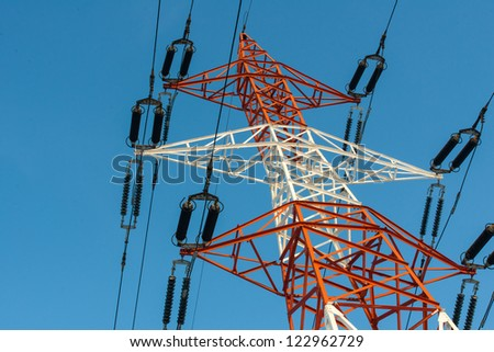 Colorful electricity pillar against blue sky. High voltage power line - stock photo