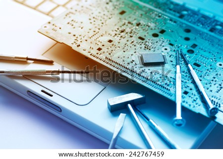 colorful electronic board and tools repairs on old laptop, vibrant concept   - stock photo