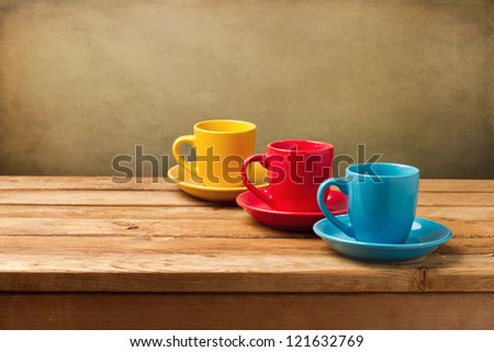 Colorful empty coffee cups on wooden table over grunge background - stock photo