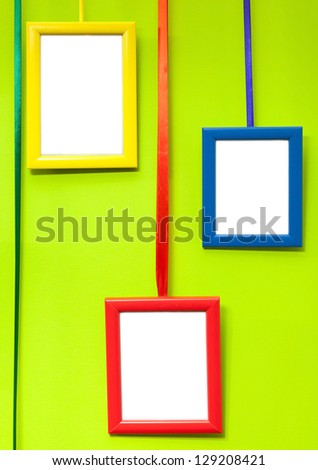 Colorful empty wooden frames on green wall - stock photo
