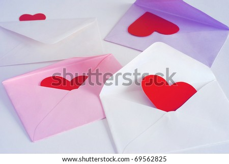 Colorful envelopes with hearts inside on a neutral background - stock photo