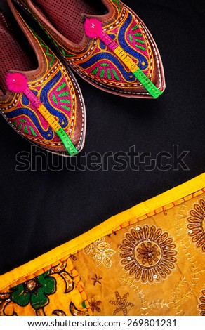 Colorful ethnic shoes and yellow Rajasthan cushion cover on flea market in India - stock photo