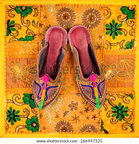 Colorful ethnic shoes on yellow Rajasthan cushion cover on flea market in India - stock photo