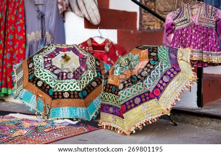 Colorful ethnic umbrellas with decorations on Rajasthan flea market in India - stock photo