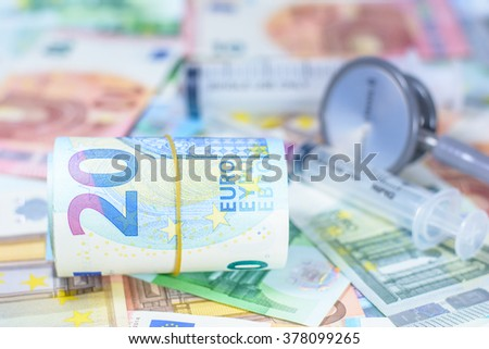 Colorful euro currency with blurry stethoscope and syringe costs for the medical insurance,Focus on number 20 of currency roll - stock photo