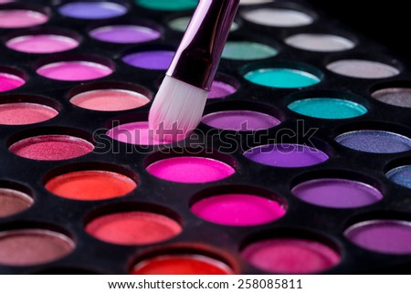 Colorful eye shadows palette with makeup brush.