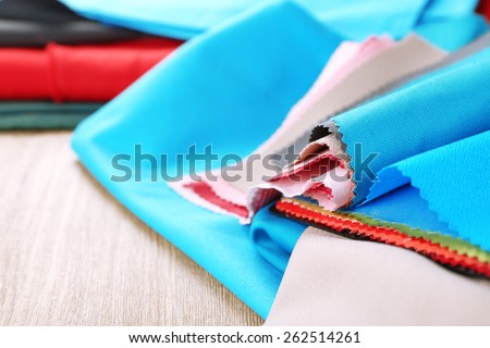 Colorful fabric samples on wooden table background - stock photo