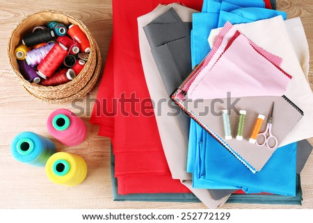 Colorful fabric samples, threads and scissors on wooden table background - stock photo