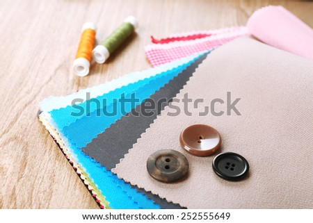 Colorful fabric samples with buttons and threads on wooden table background - stock photo