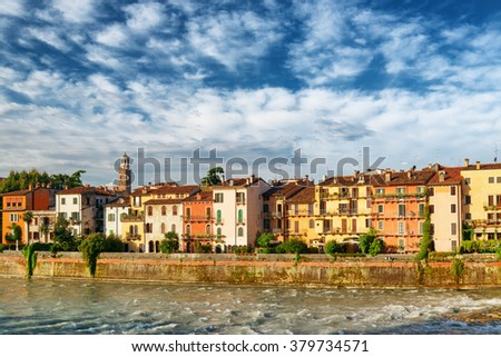 Colorful facades of old houses on waterfront of the Adige River at historic centre of Verona, Italy. Verona is a popular tourist destination of Europe. - stock photo