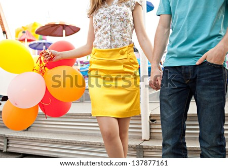 Colorful faceless view of a young couple visiting an amusement park arcade, holding balloons next to an attraction ride. - stock photo