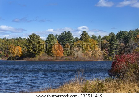 Colorful fall foliage along shoreline of lake on a sunny day in Mansfield Hollow reserve, Connecticut. - stock photo
