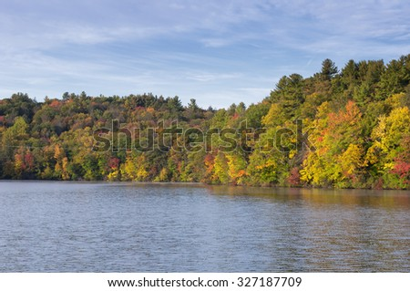 Colorful Fall foliage reflecting off the waters of Burr Pond State Park in Torrington, Connecticut. - stock photo