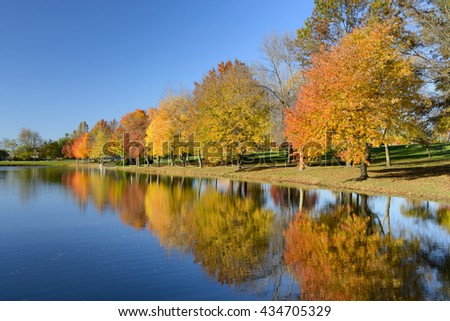 Colorful Fall Trees with Reflections in Lake - stock photo