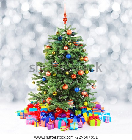 Colorful family Christmas tree surrounded by multiple gifts in the colors of the rainbow standing against a bokeh of falling fresh white snow with copyspace - stock photo