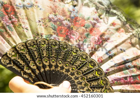 colorful fan in the hand ,colors, summer, wind, texture ,flowers ,black ,outside ,sun, hand, fingers   texture, red ,malaysian fan in hand, forest ,nature, asian fan, cute