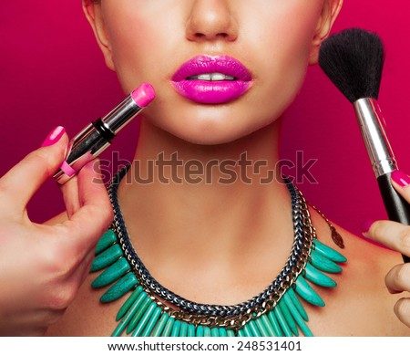 Colorful fashion beauty portrait of model with  bright make up , big pink  full lips and effect necklace .Beautiful young female getting her make-up done against color background. - stock photo