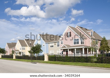 Colorful fenced in row houses with blue sky - stock photo