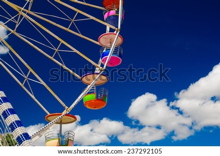 Colorful ferris wheel against a blue sky background. - stock photo