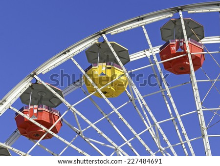 Colorful Ferris wheel against blue sky at amusement park - stock photo