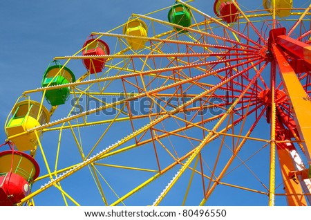 Colorful ferris wheel and blue sky - stock photo