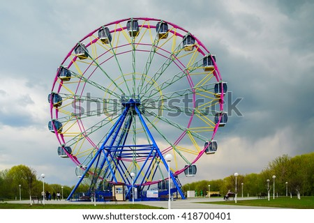 Colorful Ferris wheel in a cloudy weather with rain clouds - stock photo