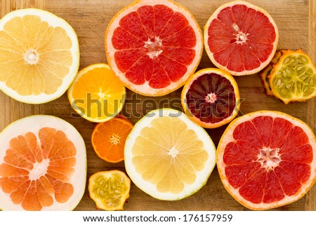 Colorful festive assortment of halved citrus fruit arranged on a wooden board with a variety of grapefruit, orange, pomelo and kiwano or horned melon viewed from above