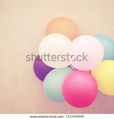 Colorful festive balloons on wall with retro instagram filter effect - stock photo