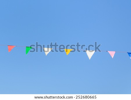 colorful festive bunting flags against a blue sky background - stock photo