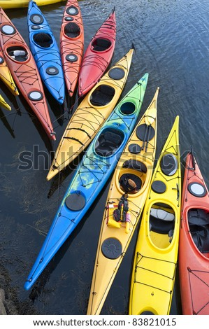 Colorful fiberglass kayaks tethered to a dock as seen from above - stock photo
