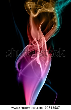 Colorful figures of smoke on a black background. - stock photo