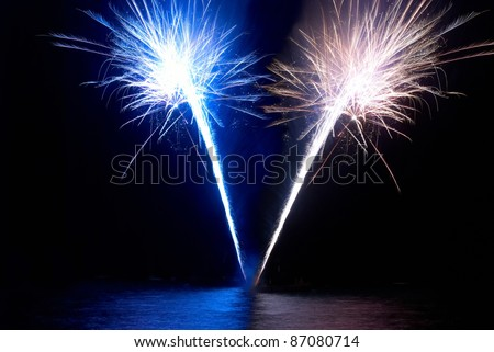 Colorful fireworks- blue and red, on the black sky background