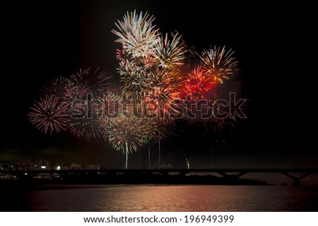Colorful fireworks burst brightly in the night sky. - stock photo