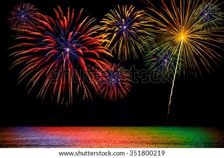 Colorful fireworks celebration on dark sea background. - stock photo