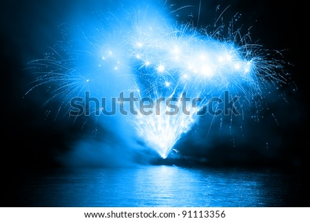 Colorful fireworks in the night sky and reflecting on the water