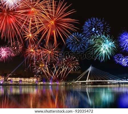 Colorful fireworks reflect from water,  beautiful bridge scenery - stock photo