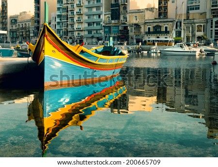 Colorful fishermen's boat reflected in water in St. Julian's Bay, Malta - stock photo