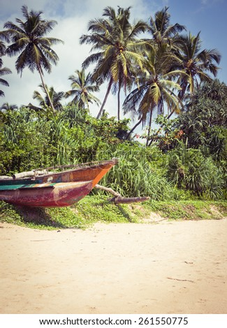 Colorful fishing boat on a tropical beach with palm trees in the background - stock photo
