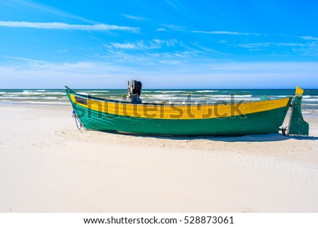 Colorful fishing boat on sandy Debki beach, Baltic Sea, Poland