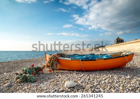 Colorful fishing boat on the beach at Chesil Cove in Portland in Dorset, at the eastern edge of Chesil Beach - stock photo