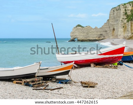 Colorful fishing boats ashore of English Channel and famous cliff La Falaise d'Amont as background. Etretat, Normandy, France - stock photo