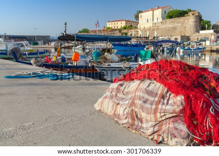Colorful fishing net laying in port of Ajaccio, Corsica. Closeup photo with shallow DOF and selective focus on a foreground - stock photo
