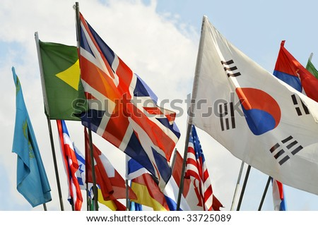Colorful Flags and a Blue Sky with Clouds on Background - stock photo