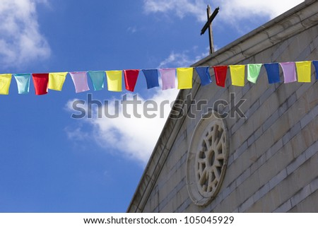 Colorful flags with a church and a deep blue sky behind - stock photo