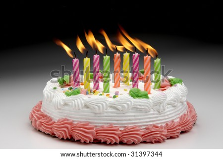 Colorful Flaming candles on a decorated cake - stock photo