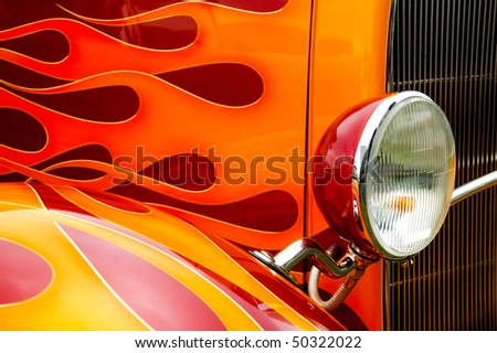 colorful flaming paintwork and headlamp on a custom hotrod - stock photo